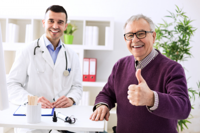 satisfied senior man with young doctor in office
